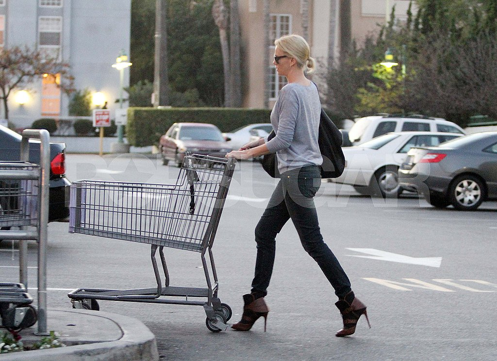 Charlize Therone returning a shopping cart
